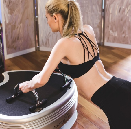Woman using Power Plate balance training system