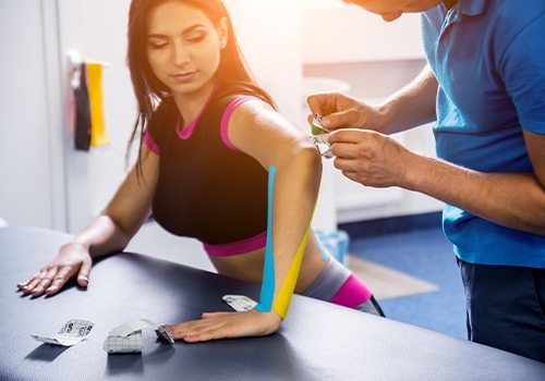 Chiropractor placing rock tape to normalize muscle tone