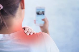 woman shoulder pain phone