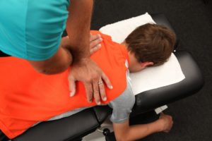 child with back pain getting an adjustment