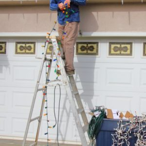 man putting up lights and avoiding shoulder injury