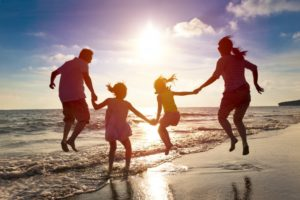 family having fun at the beach without back pain